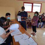 Nampak sejumlah warga Kelurahan Sa'dan Malimbong, antri mencairkan Bantuan Sosial Tunai (BST) tahap 10 di aula kantor kelurahannya dengan tetap mengikuti standar protokoler kesehatan. Warga dan petugas yang membagikan BST tetap mengatur jarak dan menggunakan masker.