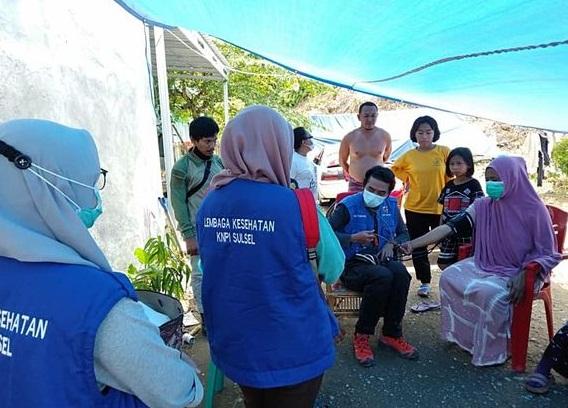 Tampak Tim Relawan Lembaga Kesehatan DPD KNPI Sulsel, melakukan pemeriksaan kesehatan warga yang menjadi korban bencana gempa di salah satu posko pengungsi di Sulbar.