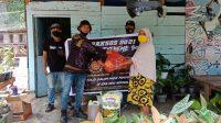 Salah satu rider motor trail yang tergabung dalam Team Ubas Extreme Luwu, menyerahkan bansos berupa paket sembako kepada warga kurang mampu, saat menggelar baksos pada wilayah Kecamatan Ponrang dan Ponrang Selatan, Kabupaten Luwu, Sabtu (06/02/2021)